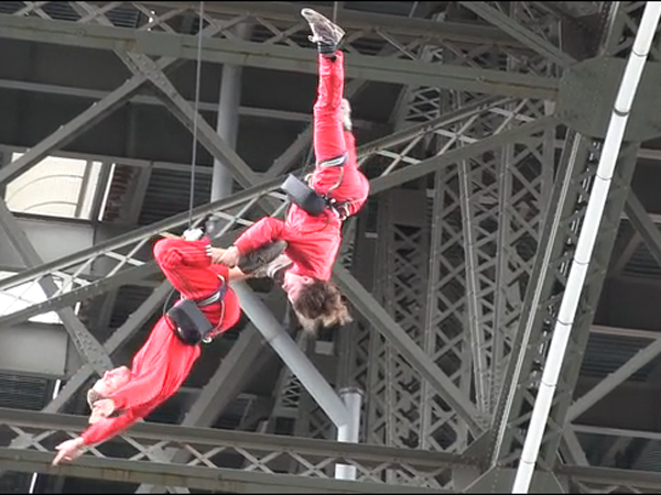 Alie and partner doing an aerial performance underneath a bridge along the Schuylkill Rive.