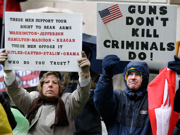 Betty and Robert Bailey of Millstone Township, N.J., hold signs during a Second Amendment rally outside the Statehouse in Trenton in Feb. 2013. (Mel Evans/AP/File)