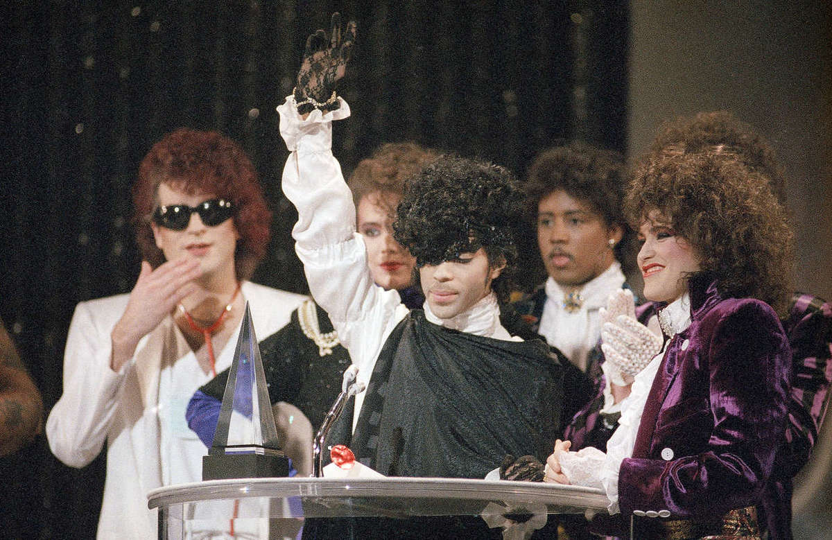 """In this Jan. 28, 1985 file photo, pop vocalist Prince holds up a hand as he and his band The Revolution accept the American Music Award for best single """"When Doves Cry"""" in Los Angeles. The Revolution is preparing to kick off a spring U.S. tour with a performance Friday, April 21, 2017, at Paisley Park in the Minneapolis suburb of Chanhassen, on the first anniversary of the Prince´s death from an accidental painkiller overdose."""