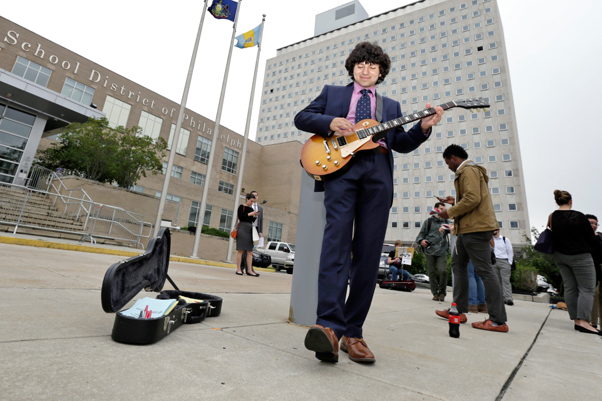 Masterman School 12th grader Nick Vicoli plays his guitar in support of music in the schools prior to the School Reform Commission meeting to adopt a budget.