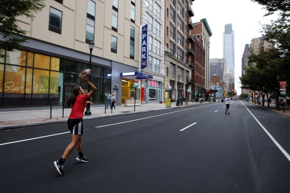 Playing football along the 1200 block of Arch Street near the Pennsylvania Convention Center with no cars around during the papal visit on Friday, September 25, 2015.