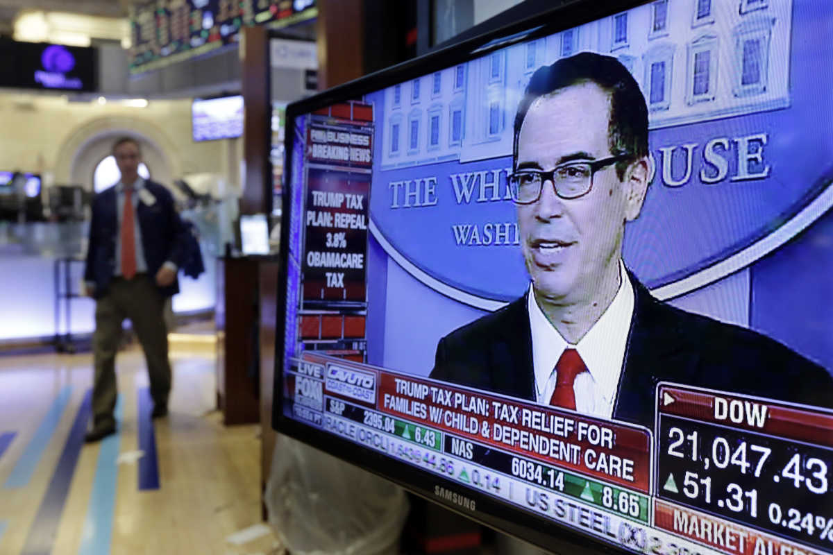 Treasury Secretary Steven Mnuchin appears on a television screen on the floor of the New York Stock Exchange on Wednesday.<br />