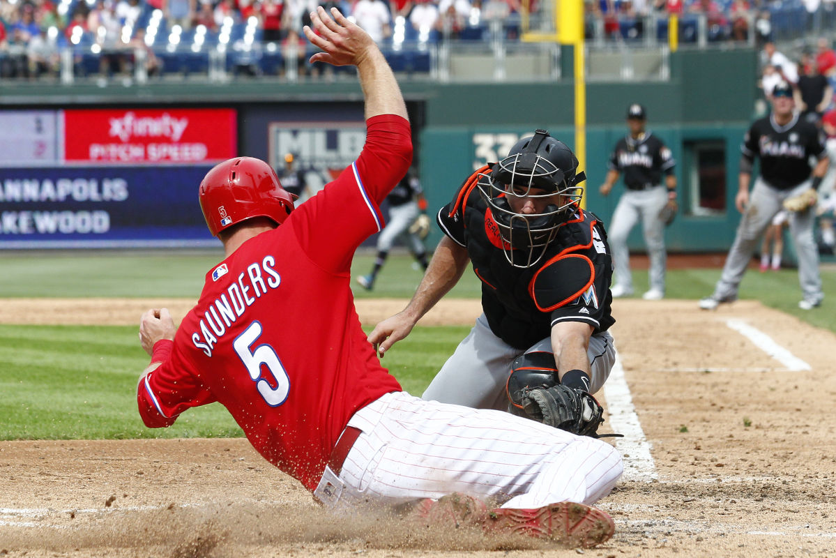 The Phillies' Michael Saunders slides in safely at home past Marlins catcher J.T. Realmuto during the sixth inning of Thursday's game at Citizens Bank Park.