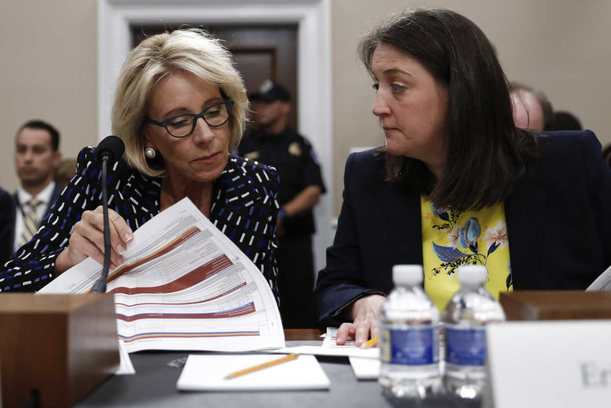 Education Secretary Betsy DeVos (left), accompanied by Education Department Budget Service Director Erica Navarro, looks over her notes Wednesday on Capitol Hill.<br />