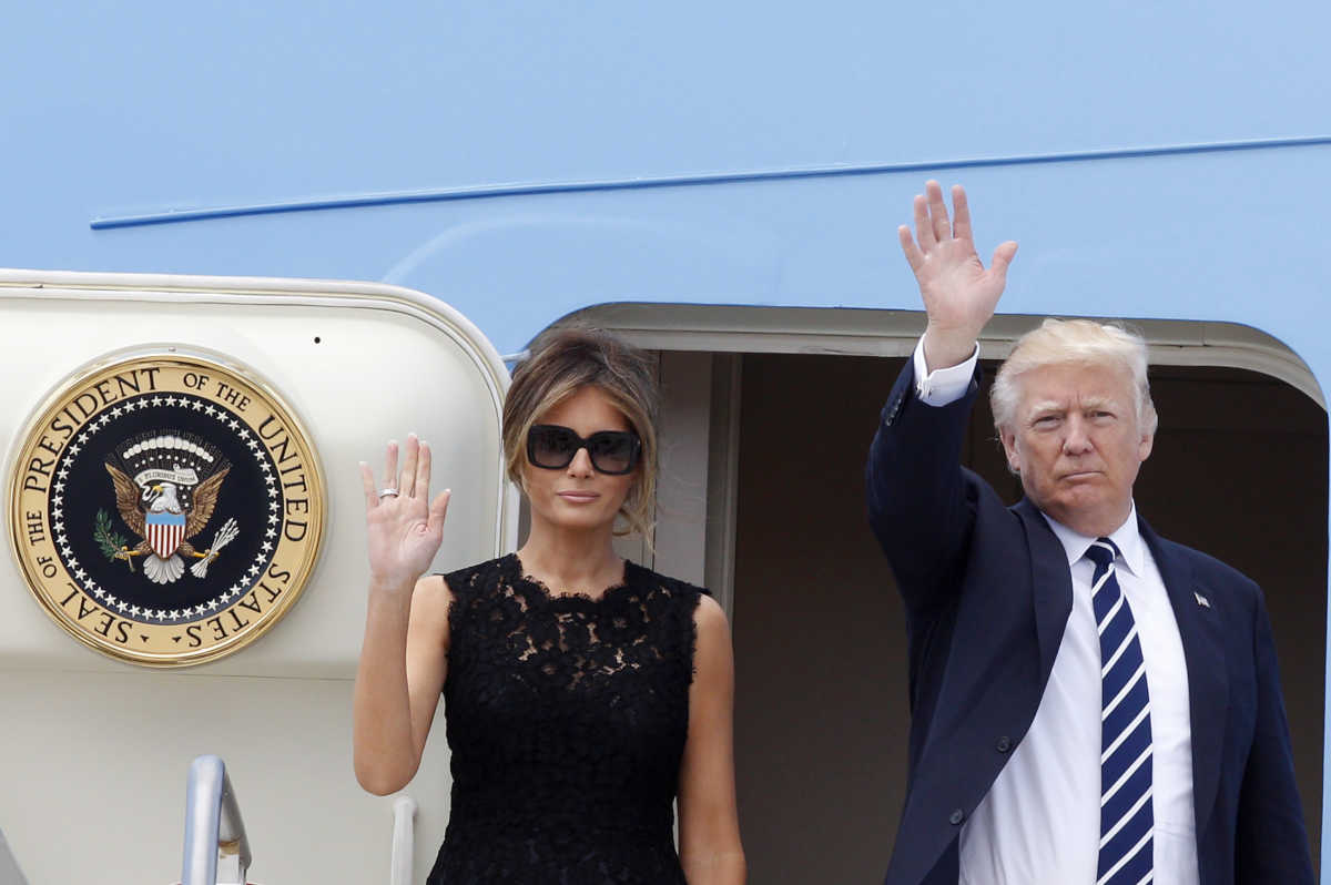 President Trump and first lady Melania Trump wave to reporters before boarding Air Force One to Brussels, at the end of a two-day visit to Italy.<br />