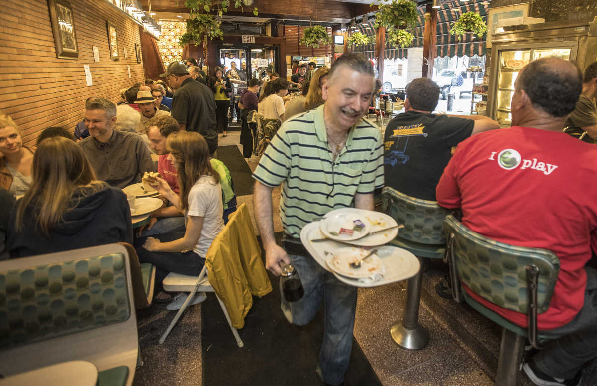 Little Pete´s Restaurant co-owner John Koutroubas, center, buses a table during the busy morning crowd at Little Pete's on the final day of business for the restaurant on Monday May 29, 2017.