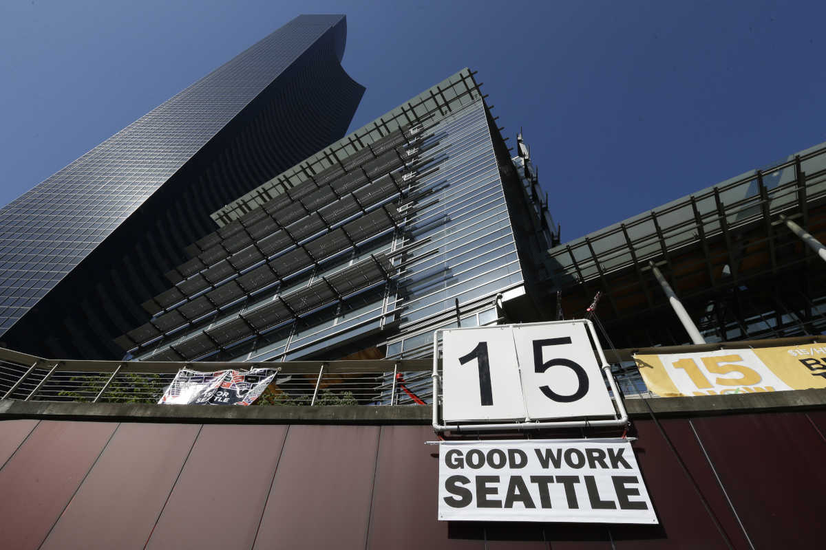 "In this June 2, 2014, file photo, a sign that reads ""15 Good Work Seattle"" is displayed below Seattle City Hall (right) and the Columbia Center building after the Seattle City Council passed a $15 minimum wage measure."