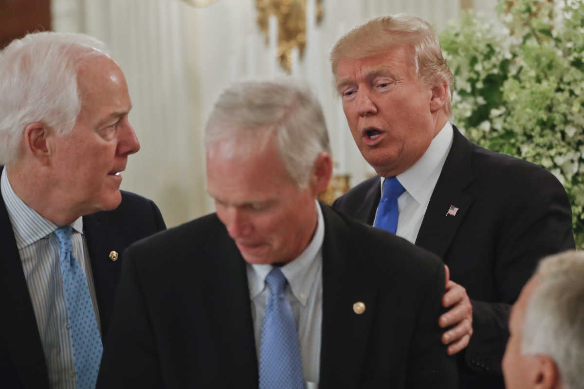 President Trump stops to greet Senate Majority Whip John Cornyn of Texas (left) and Sen. Ron Johnson (R., Wis.) at a luncheon with GOP leadership Wednesday in the State Dinning Room of the White House in Washington.