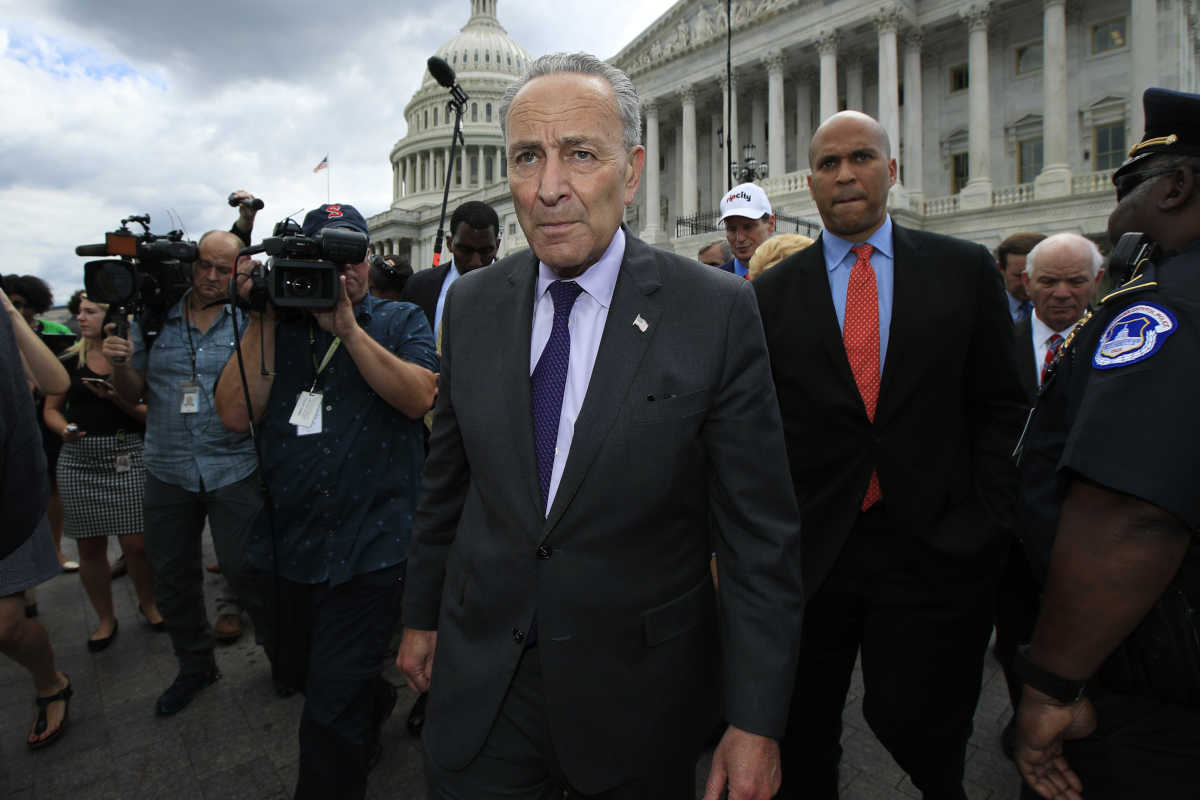 Senate Minority Leader Chuck Schumer leads fellow Democratic senators to meet supporters outside the Capitol on Tuesday after the Senate voted to start debating Republican legislation to tear down much of  the Affordable Care Act.<br />