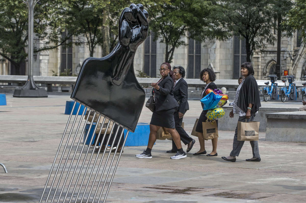 "Pedestrians walk across Thomas Paine Plaza across from City Hall on Tuesday, Sept.12, 2017, and notice the new piece of art, ""All Power to All People,"" by Hank Willis Thomas."