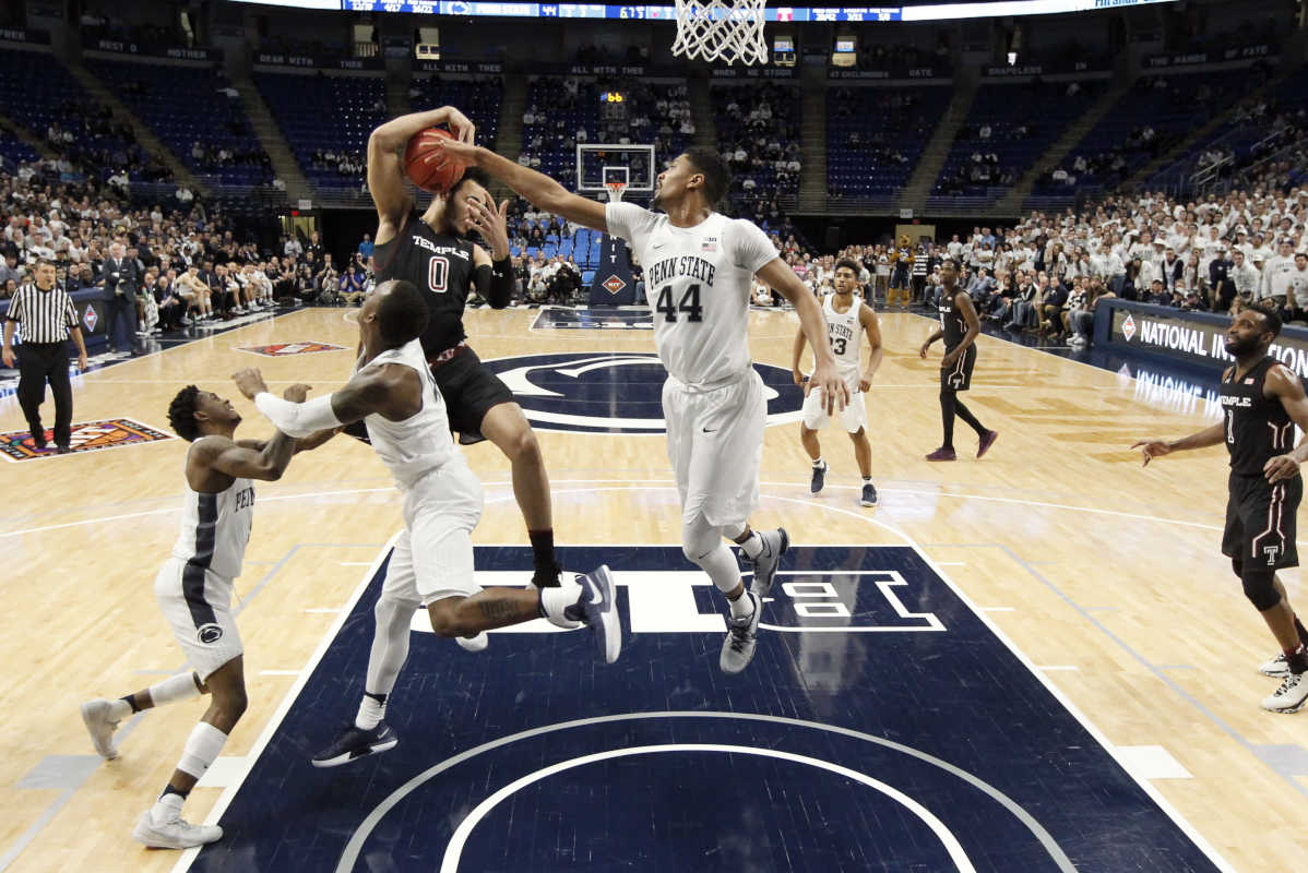 Temple's Obi Enechionyia (0) grabs a rebound in front of Penn State's Julian Moore (44) and Nazeer Bostick, second from left, during the second half of an NCAA college basketball game in the first round of the NIT in State College, Pa., Wednesday, March 14, 2018. Penn State won 63-57. (AP Photo/Chris Knight)