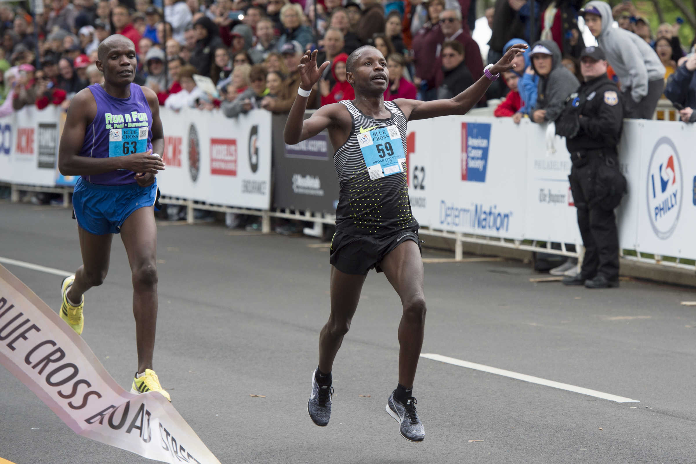 Dominic Korir (right) beats out Philip Mburu to finish first in the field of nearly 40,000 runners participating in the 38th annual Blue Cross Broad Street Run May 7,2017.