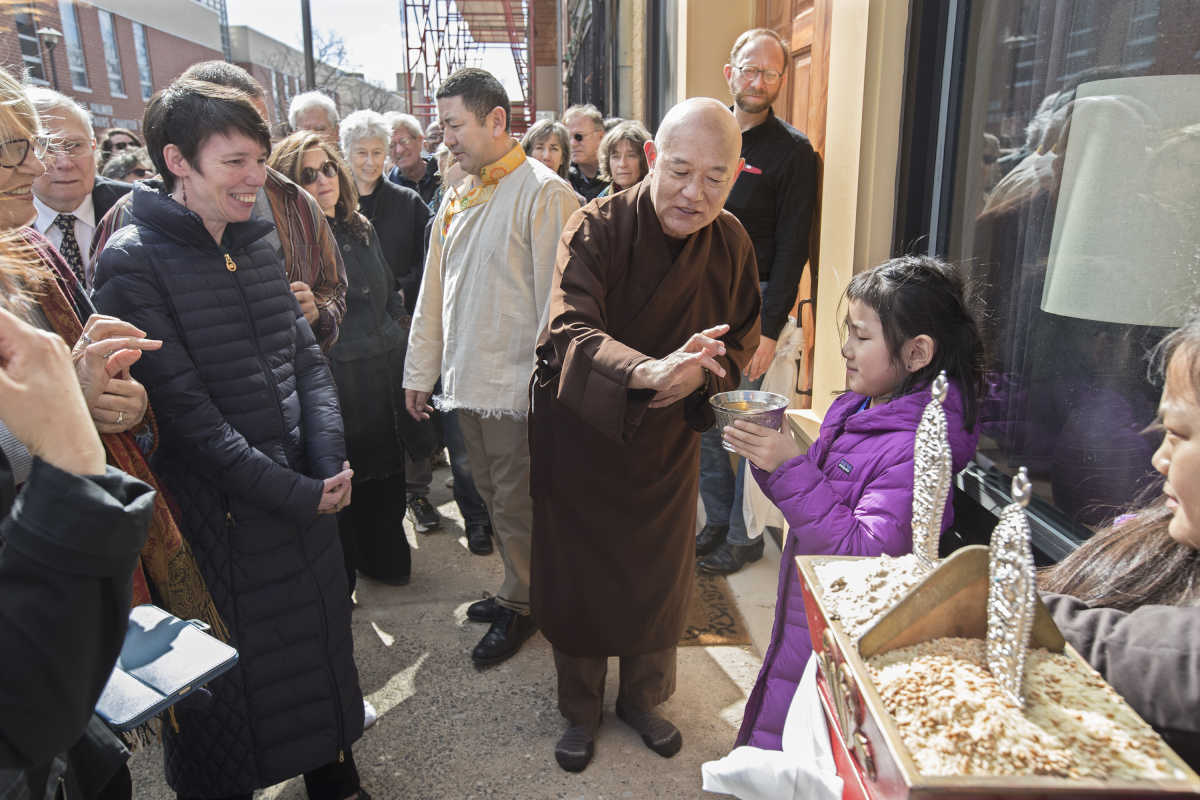 Tibetan monk Losang Samten (center) shows the assembled members of the Tibetan Buddhist Center of Philadelphia how to place your finger in the bowl of Tibetan beer, held by Tenzin Yangdon, 7,  and then to flick the liquid into the air as a celebration of their new home on North Marshall Street in Philadelphia.