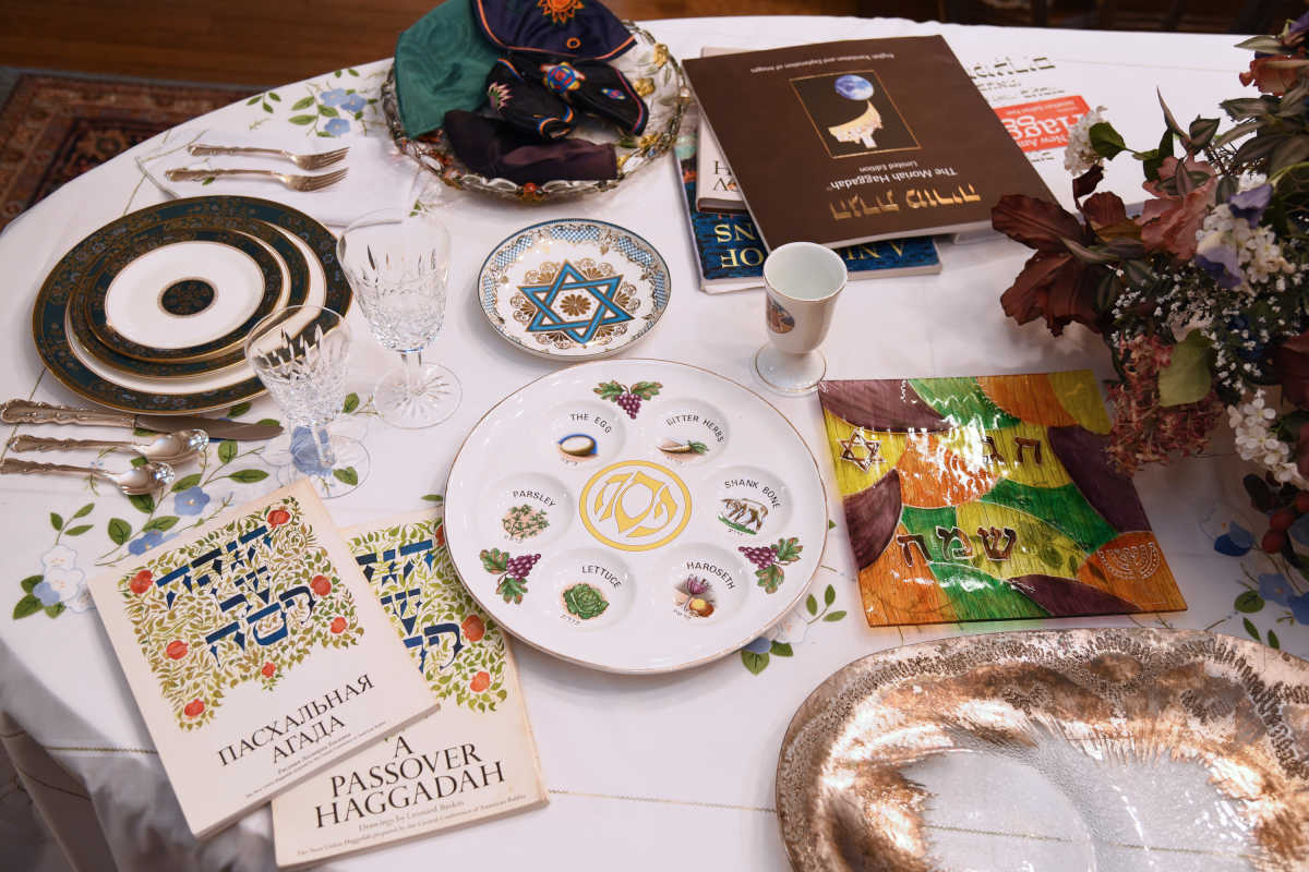 The Passover Seder table in the dining room of the Judaica-filled home of Phyllis and Michael Levy. There are many Haggadot (Passover prayer books), including a Russian version of their favorite (left- with Leonard Baskin drawings) from when they hosted a family from the former Soviet Union. Also a seder plate (center) from Phyllis' mother and a serving plate (right) from Michael's Bubbe - grandmother, Bubbe - grandmother - given to the couple as an engagement present (it is usually used for the brisket).