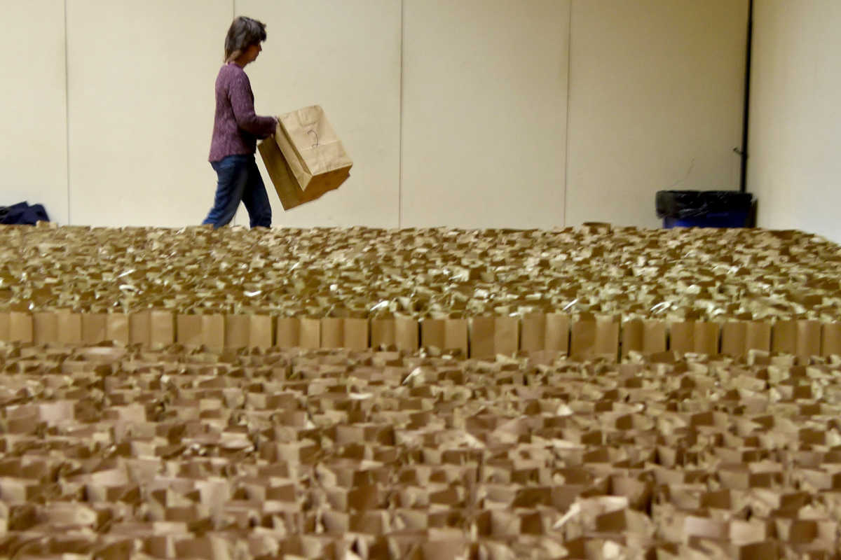 Bonnie Greisler of Huntingdon Valley helps line up hundreds of empty grocery bags early Sunday morning at Temple Sinai in Dresher, where 400 volunteers soon fill them with eight days of Passover food for 600 needy families.