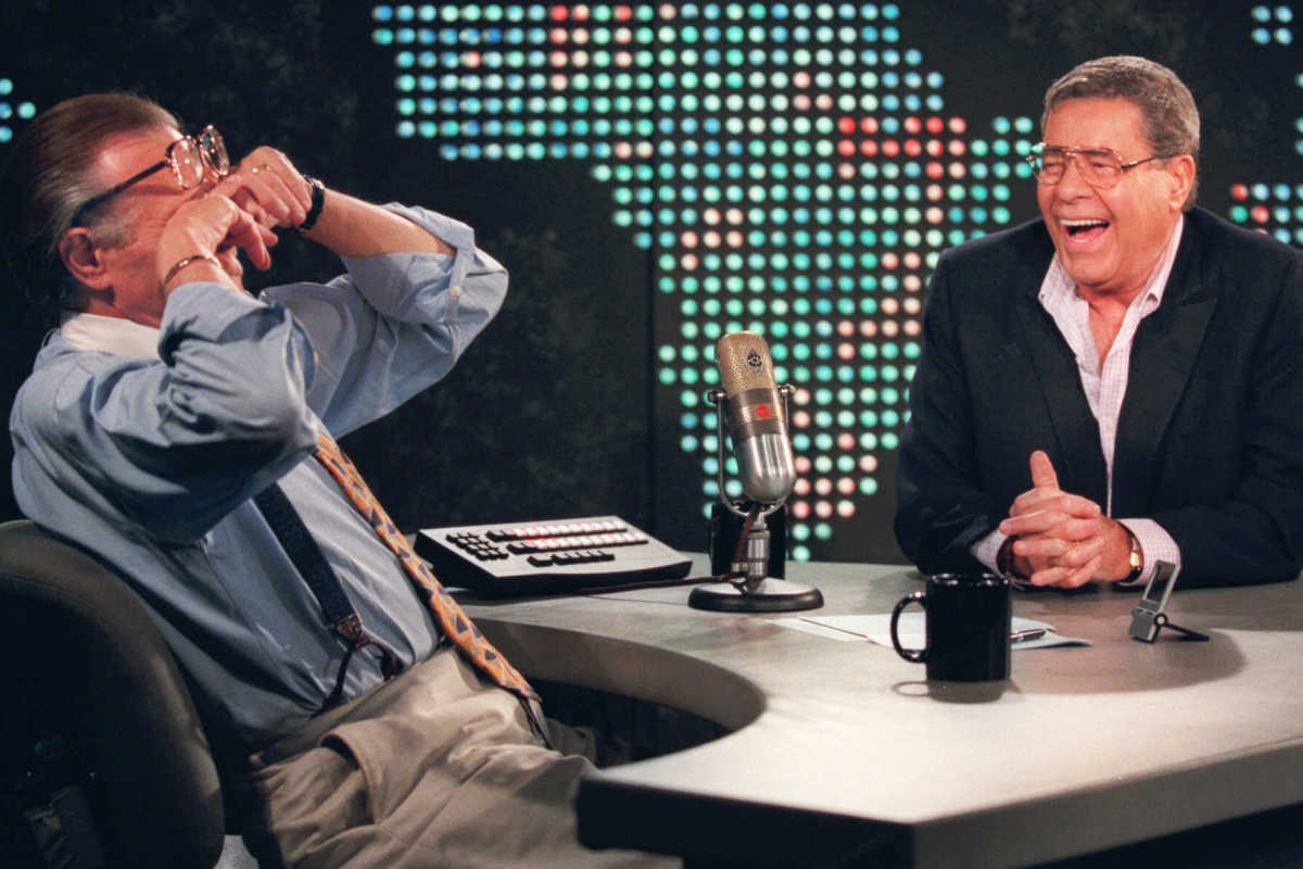 """Larry King wipes his eyes after laughing at a joke by comedy legend Jerry Lewis on Aug. 26, 1999 on the set of """"Larry King Live"""" at CNN Studios in Los Angeles."""