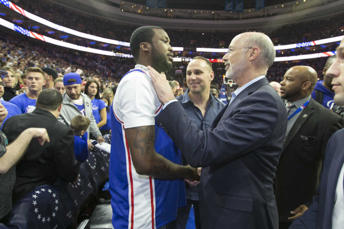Rapper Meek Mill (left) talks with Gov. Wolf before the playoff game between the Sixers and the Miami Heat at the Wells Fargo Center on April 24, 2018.