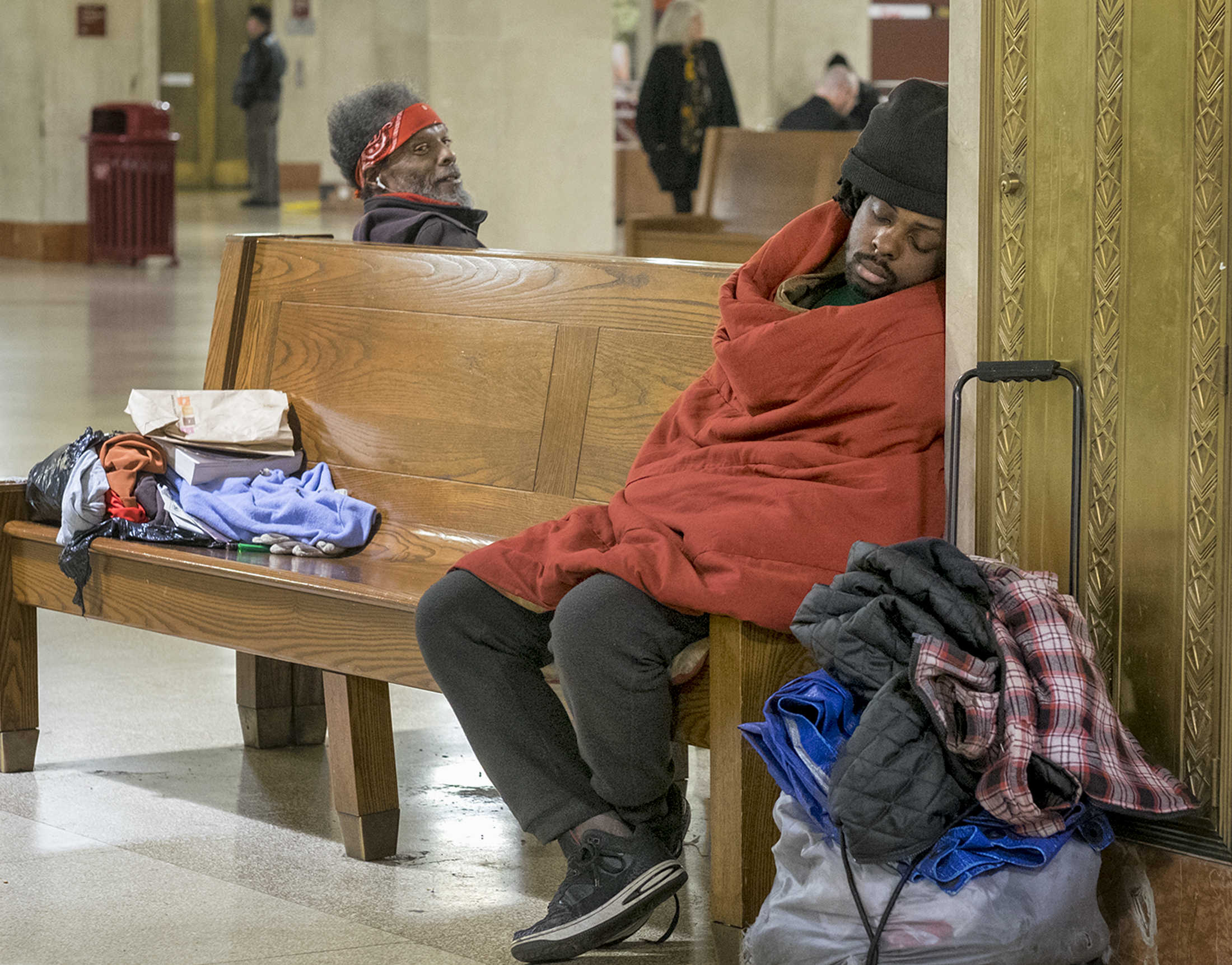 At Suburban Station, an unidentified homeless man sleeps on a bench.The Philly Shrug adds to the invisibility of homelessness.<br />