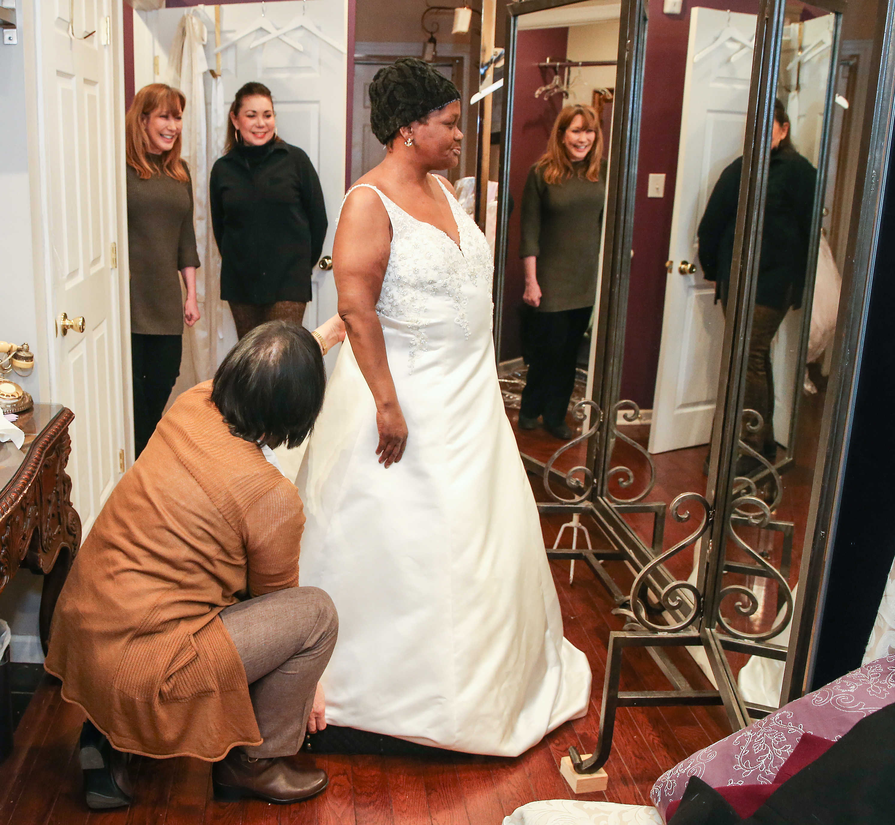 Sharon Suleta (top left) and Carolyn Verdi (top right) watch as seamstress Mira Dieterle fits Maria Isaacs' wedding gown.