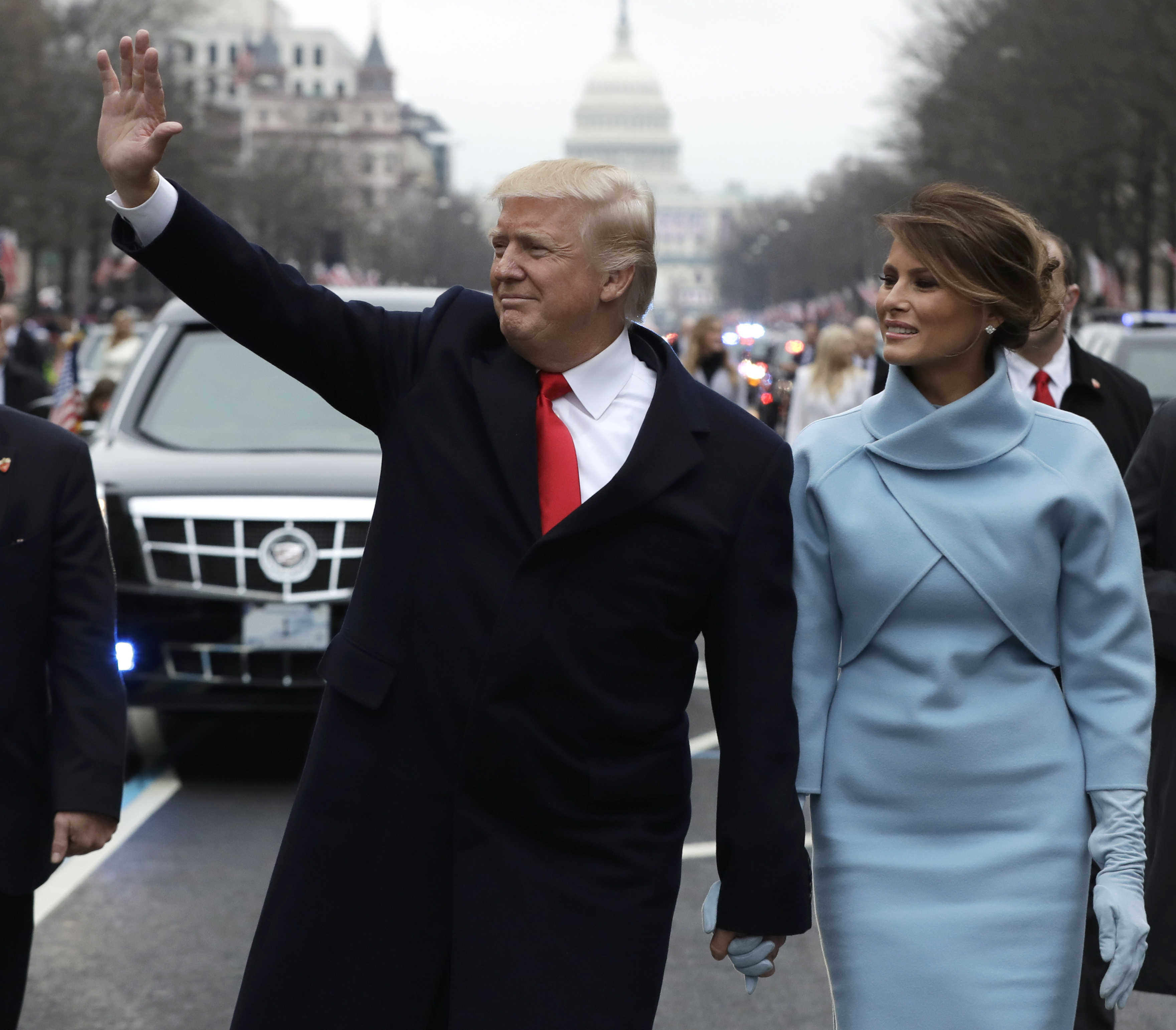 FILE- In this Jan. 20, 2017, file photo, President Donald Trump waves as he walks with first lady Melania Trump during the inauguration parade on Pennsylvania Avenue in Washington. Trump raised $107 million for his inaugural festivities. Trump's inaugural committee is due to file information about those donors with the Federal Election Commission and said it would do so on Tuesday, April 18. (AP Photo/Evan Vucci, Pool, File)
