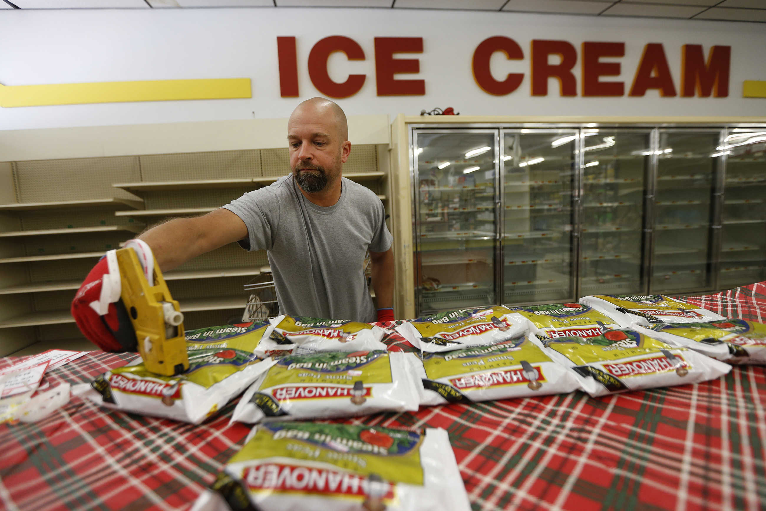 Store owner Jim McCouch marks down items during the last days of Perk's Family Market, in Pine Hill.
