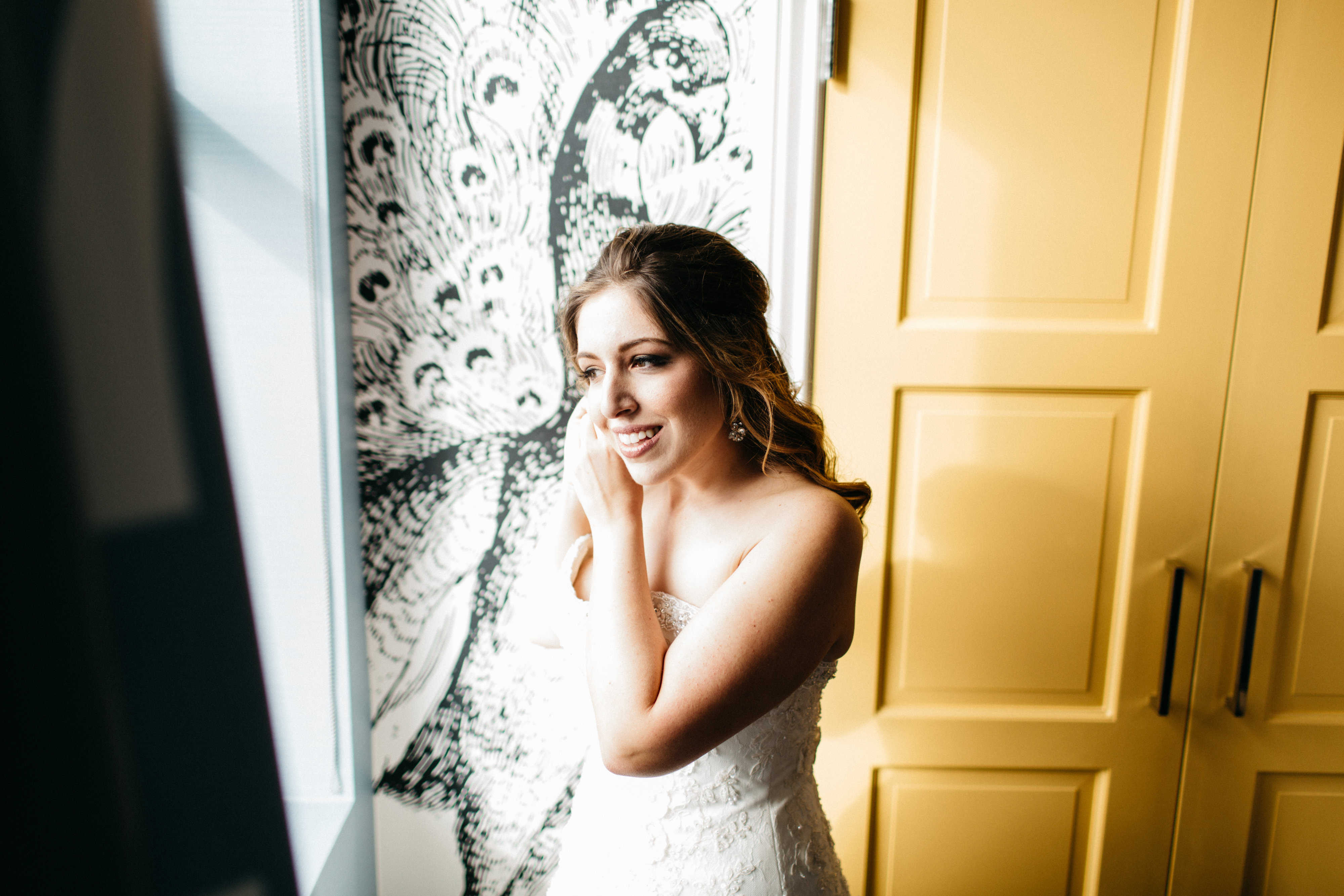 Samantha Giusti  poses by a window on her wedding day.
