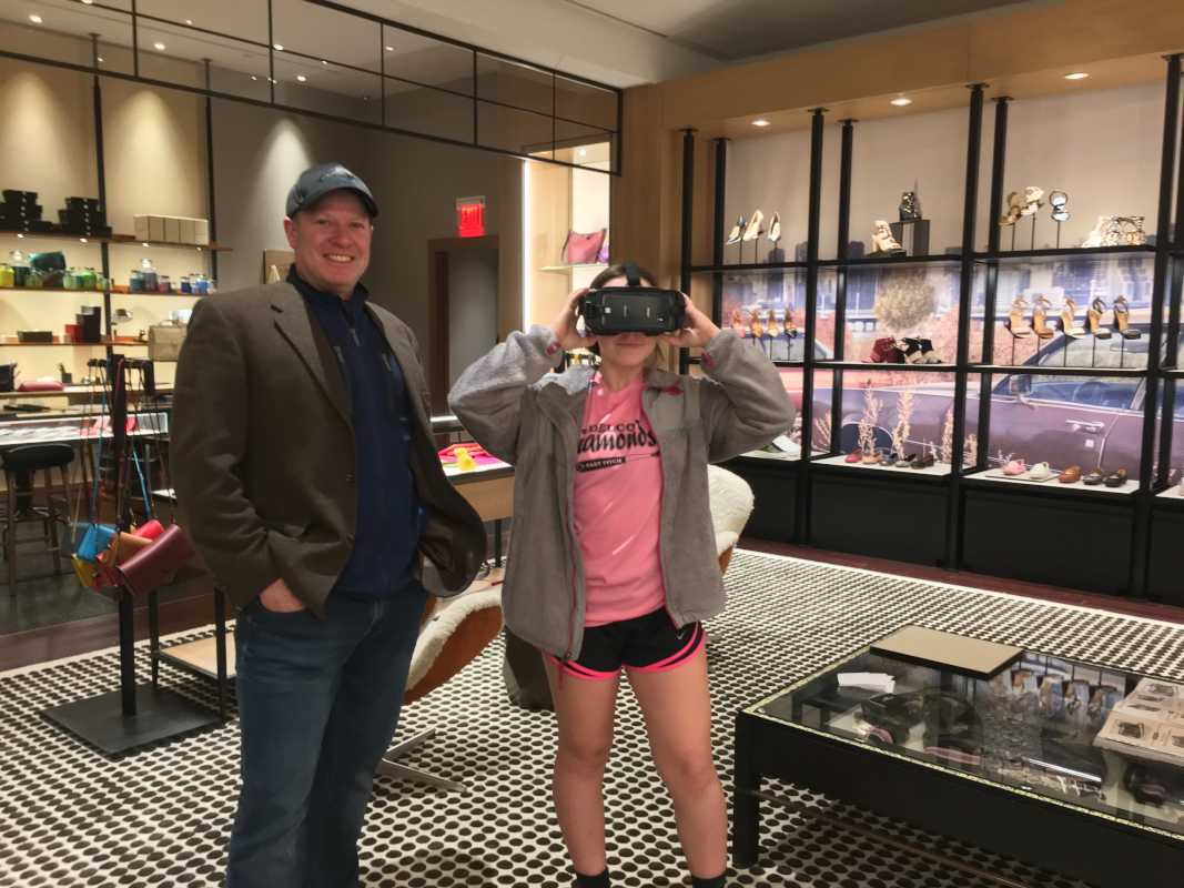 Carly Rosenberger, 13, of Conshohocken, takes the COACH Virtual Reality tour of last month's New York Fashion Week featuring COACH's fall collection while her dad, Matthew Rosenberger, 49, looks on.(Suzette Parmley, Staff)