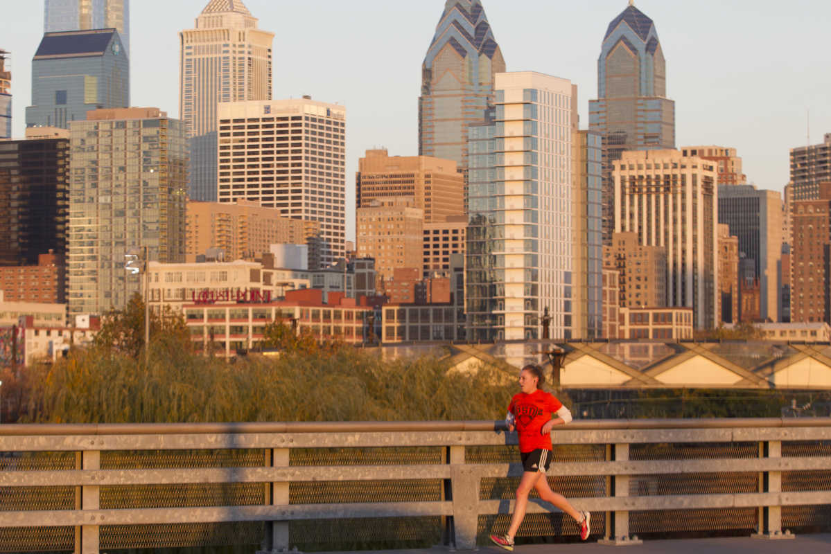 A jogger on the South St. Bridge on Nov.17, 2016 with the city bathed in the light of the setting sun.