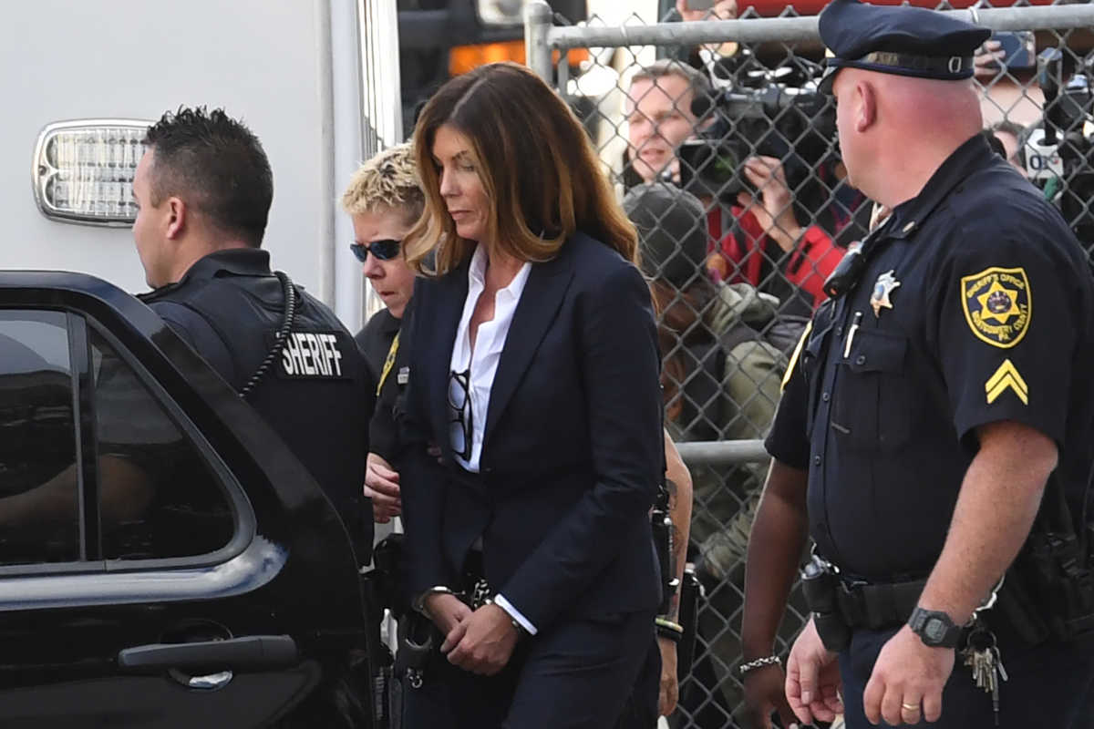 Former Pennsylvania Attorney General Kathleen Kane is led out of the Montgomery County Courthouse in handcuffs after being sentenced Monday to 10 to 23 months in jail.