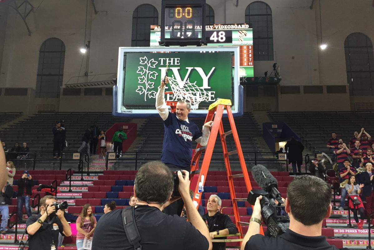 Penn women's basketball coach Mike McLaughlin celebrates after cutting down the net at the Palestra.