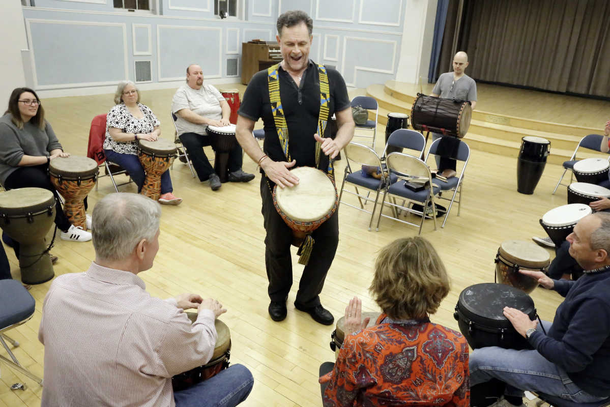 Settlement Music School percussion faculty member Bill Marconi (standing) gets the students acquainted with the African djembe drum during the Queen Village Community Drum circle on February 24, 2017.