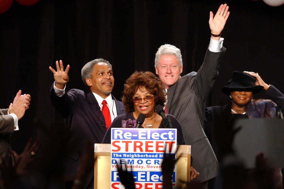 Mayor John Street, left, and former President William Clinton wave to  the cameras and crowd during a rally to help re-elect Mayor Street at the Marriott Hotel in Philadelphia on October 31, 2003. Introducing them is radio host Mary Mason.