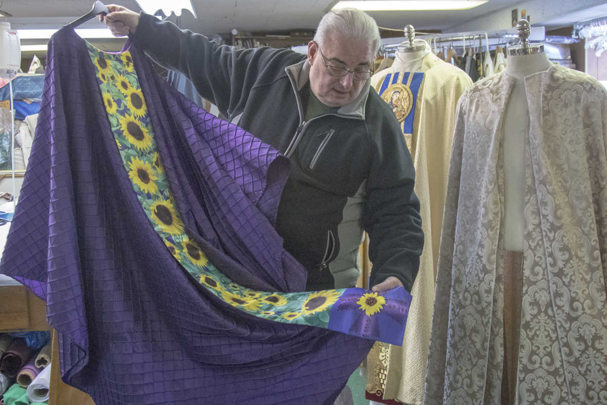 Father Richard Cannuli displays one of the clergy vestments he designed, featuring sunflowers on the stole. Father Cannuli currently works out of his art studio in a gatehouse adjacent to an Augustinian residence near the Villanova University campus.