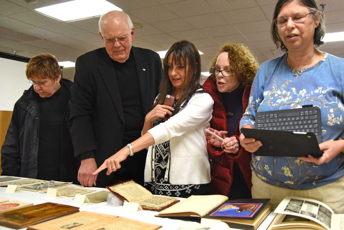 "Dr. Ierachmiel ""Yerach"" Daskal (second from left), of Elkins Park, talks with attendees at his lecture and opening of an exhibit of Daskal's collection of historic Haggadot at Gratz College. Haggadot are the books used during a Passover seder to guide those gathered through the holiday meal."