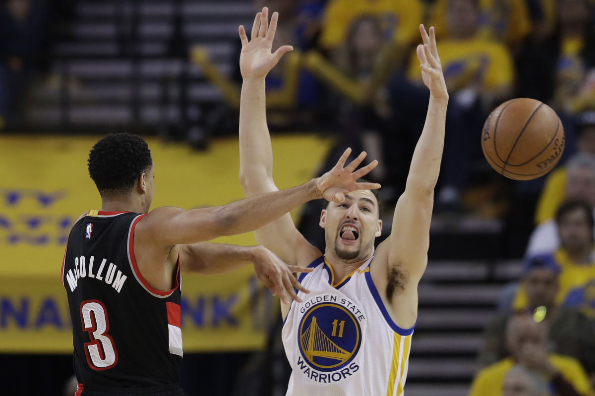 The Trail Blazers´ C.J. McCollum (3) passes the ball as Golden State Warriors´ Klay Thompson defends during the first half in Game 2.