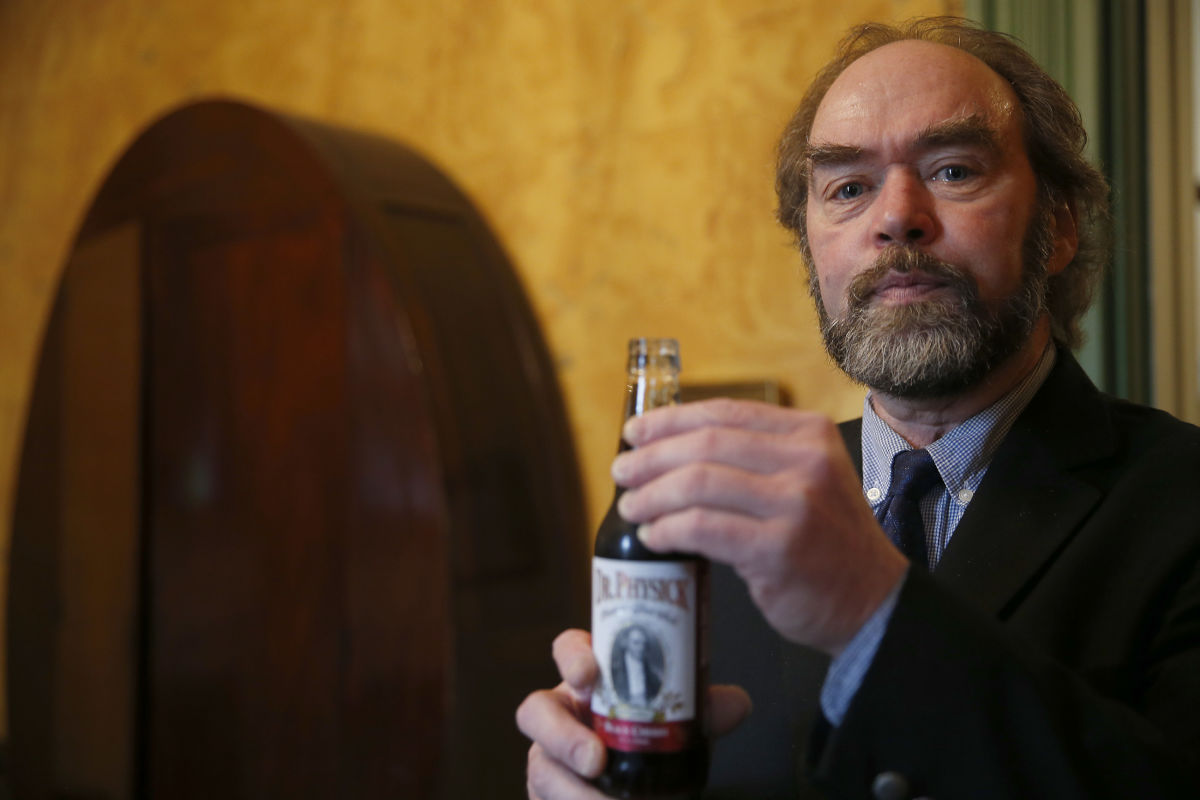 "J. Del Conner, descendant of Dr. Philip Syng Physick, who was the ""Father of American Surgery,"" holds a black cherry soda in the Hill-Physick. Conner is the caretaker of the family name, including the family soda recipe. he worries the soda tax may end the family fizz."