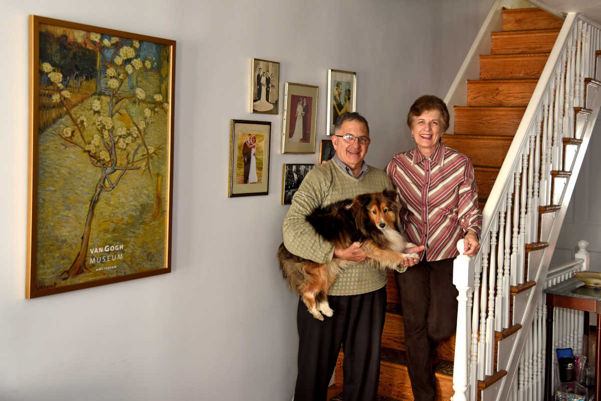 Elena and Joseph Cappella pose in their Fitler Square home with their Sheltie, Nessie, a certified therapy dog Elena works with.
