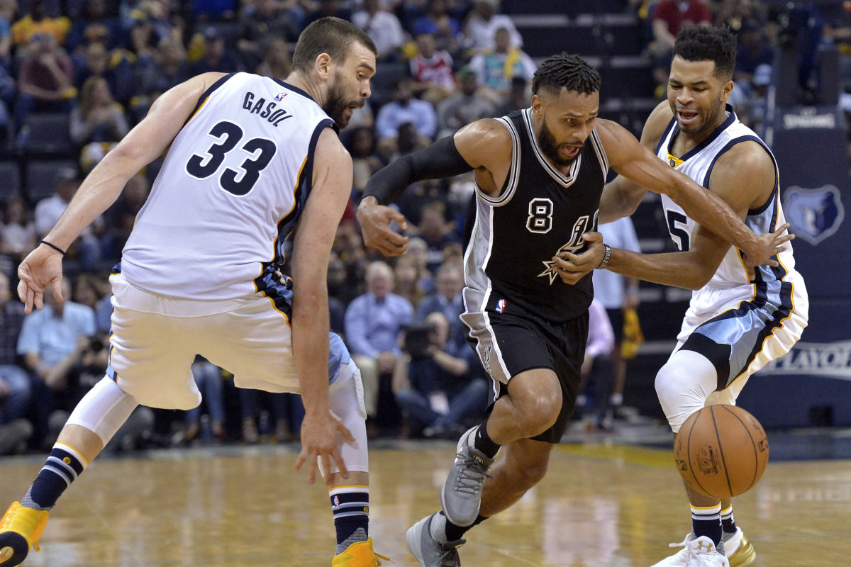 Spurs guard Patty Mills (8) looses control of the ball while driving between the Grizzlies´ Marc Gasol (33) and Andrew Harrison during second-half action of Game 3.