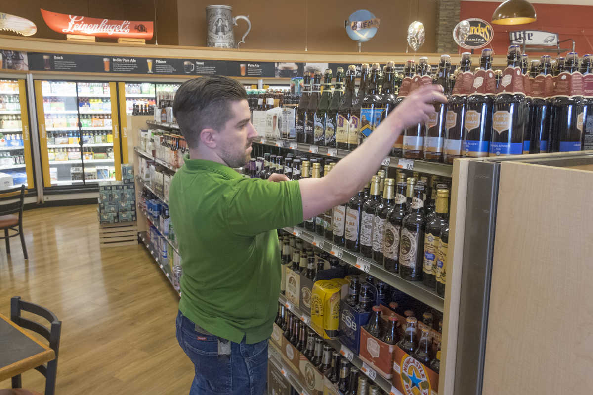 Ian Meekim, lead beer-garden employee at the Giant in Exton, reviews the selection at the store.