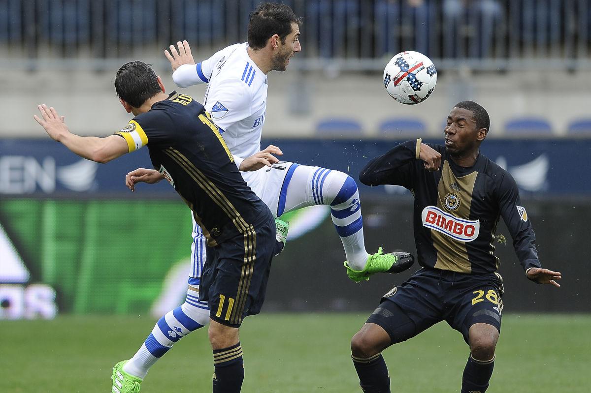 Montreal Impact midfielder Ignacio Piatti kicks the ball past Philadelphia Union defender Ray Gaddis and midfielder Alejandro Bedoya.