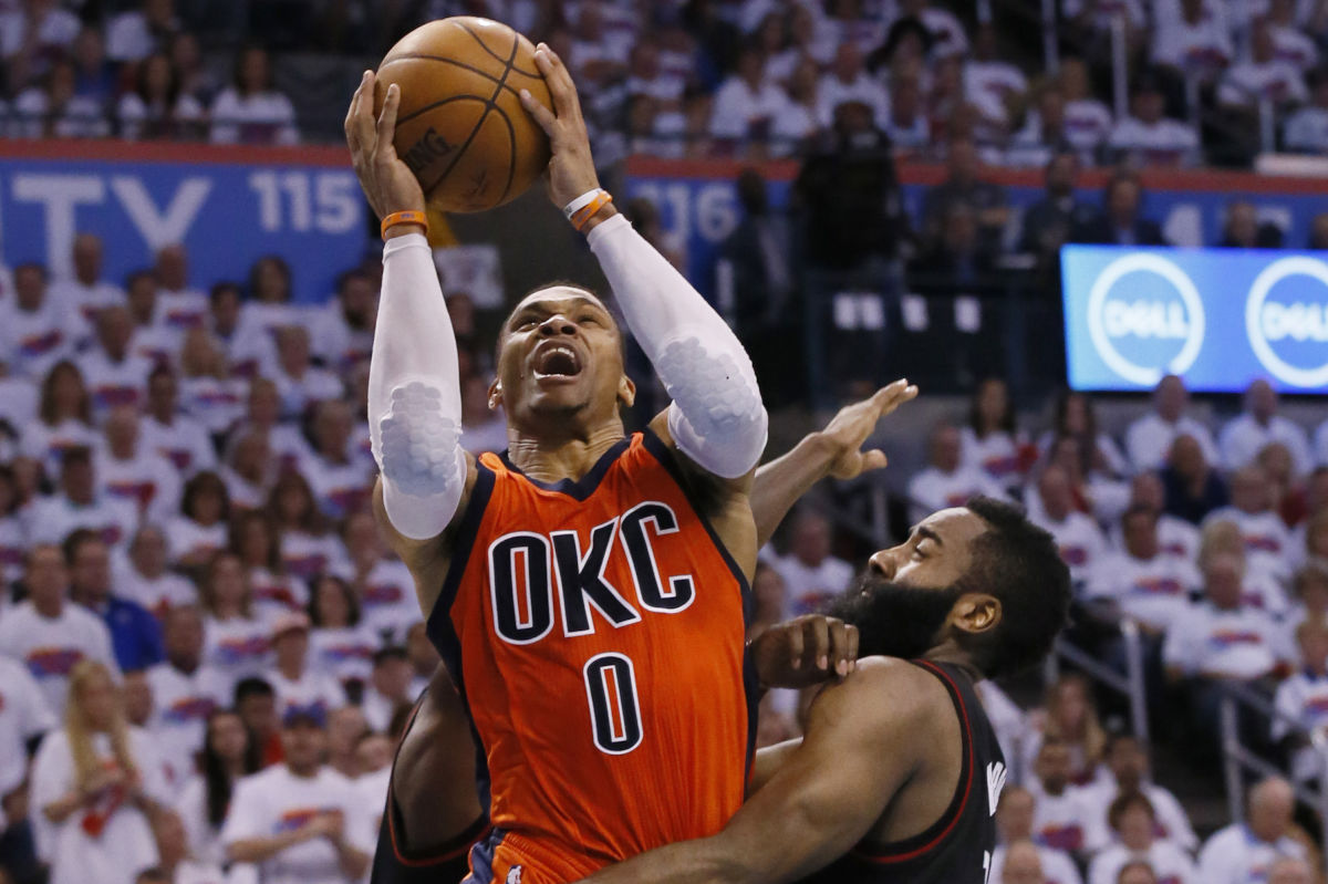 Oklahoma City Thunder guard Russell Westbrook (0) shoots between Houston Rockets guards Patrick Beverley (rear), and James Harden (right) in the fourth quarter of Game 4 of a first-round NBA basketball playoff series in Oklahoma City, Sunday, April 23, 2017.