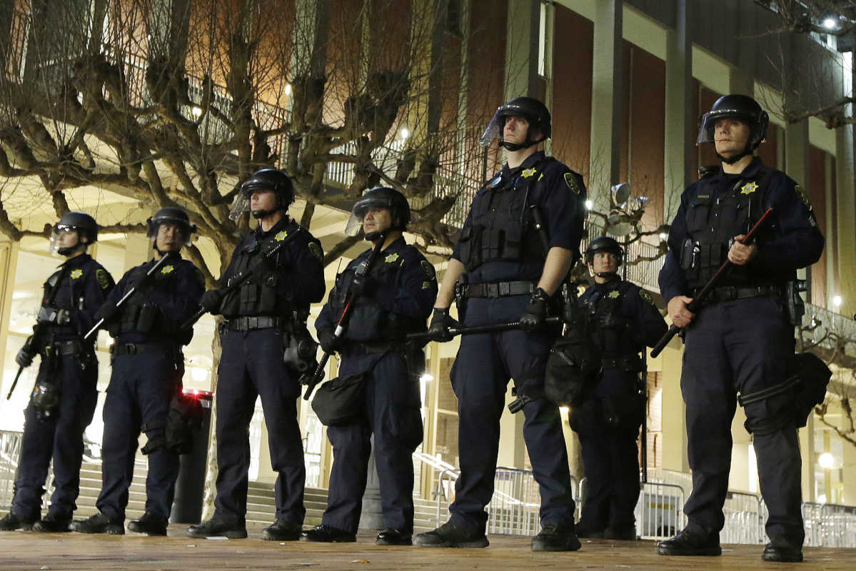 In this Feb. 1, 2017 file photo, University of California, Berkeley police guard the building where Breitbart News editor Milo Yiannopoulos was to speak.