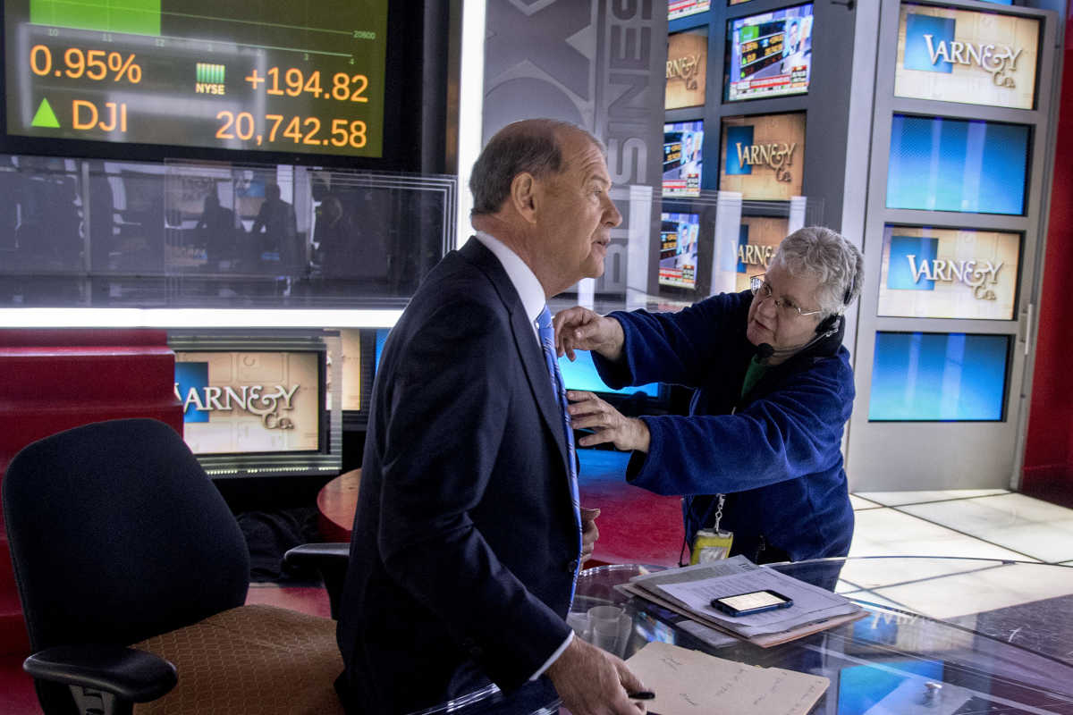 Fox Business Network anchor Stuart Varney (left), on the set of his show Varney & Company at the 21st Century Headquarters in New York, gets helps with his microphone.
