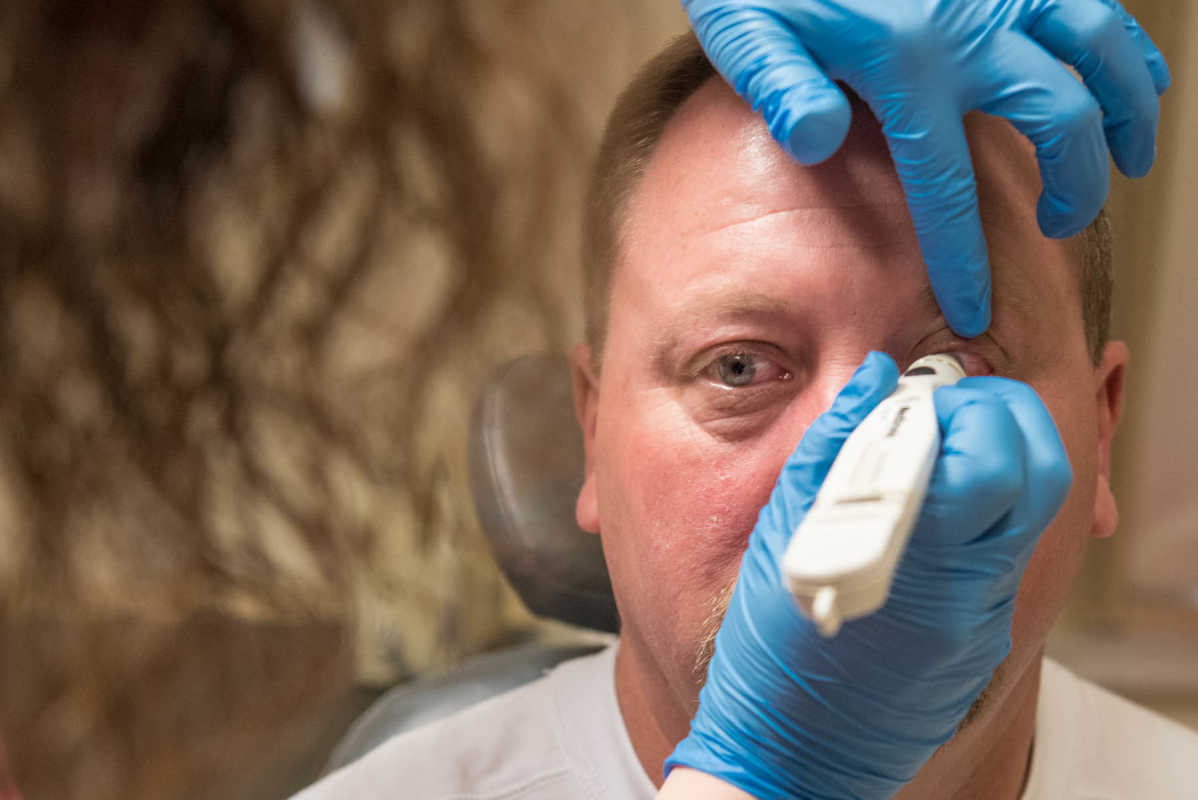 Ocular melanoma patient Ed Tuggle receives a painless last check of his eye pressure before the laser activates the cancer drug, made of virus-like particles that home in on the tumor.