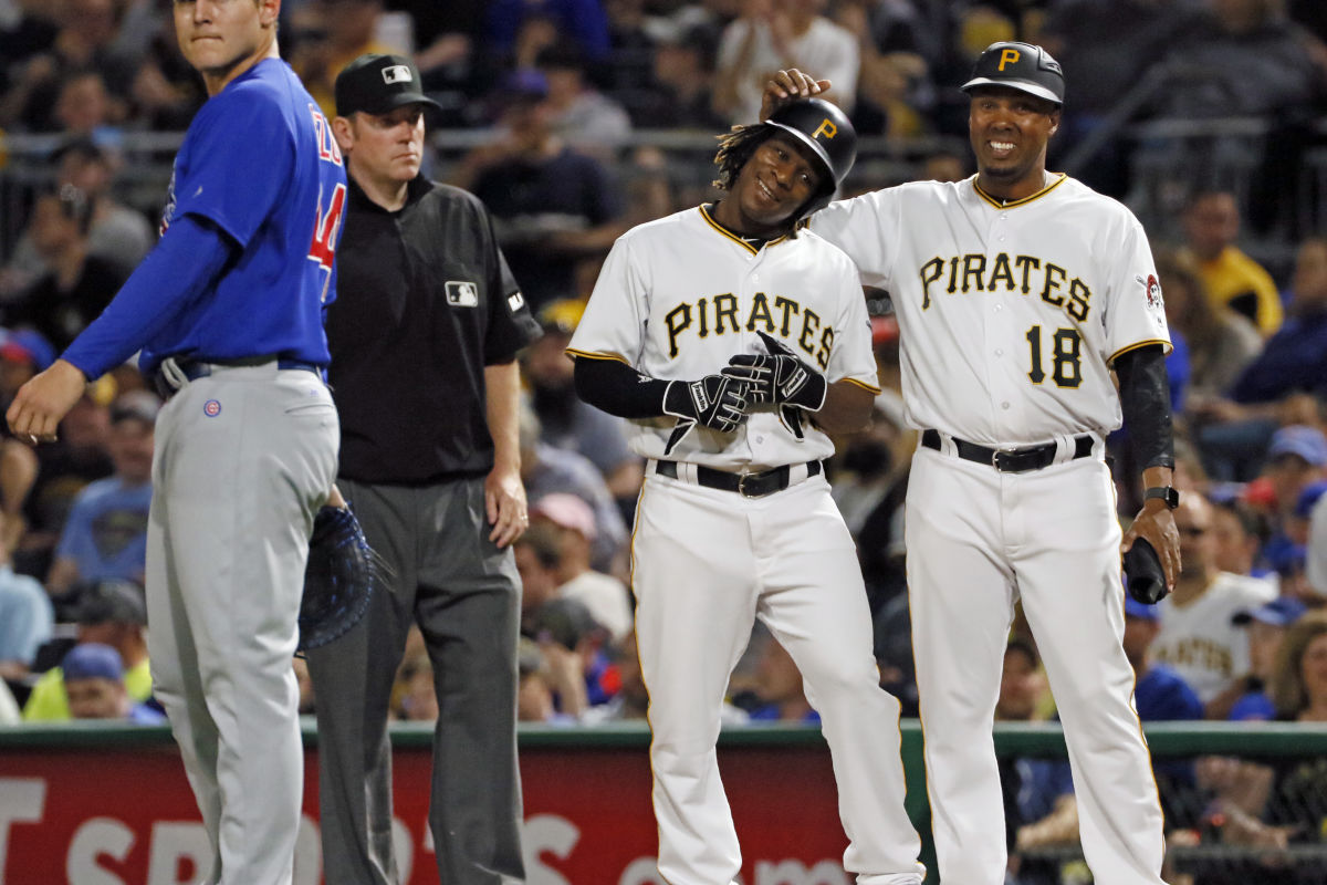 Pittsburgh Pirates´ Gift Ngoepe, a native of South Africa, and the first baseball player from the continent of Africa to play in the Major Leagues, receives congratulations from first base coach Kimera Bartee (18) after getting a single off Chicago Cubs starting pitcher Jon Lester in his first Major League at-bat in the fourth inning of a game in Pittsburgh, Wednesday, April 26, 2017.