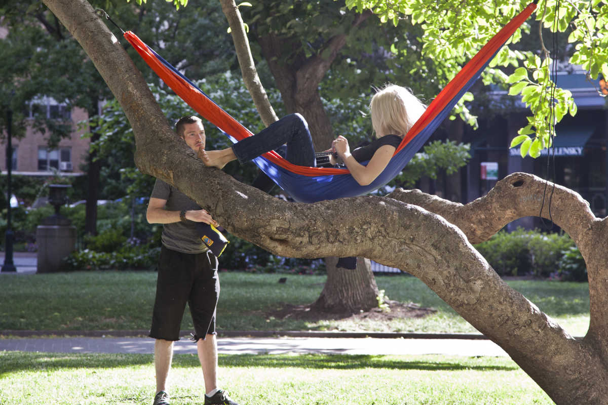 A couple lounges in their own hammocks strung in the trees of Rittenhouse Square.