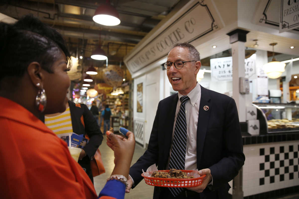 DA candidate Michael Untermeyer, right, talks with Etrusia Gibbs, left, of Philadelphia, as he campaigns at The Famous 4th Street Cookie Company in the Reading Terminal last month. Untermeyer became part owner of the cookie company last year.