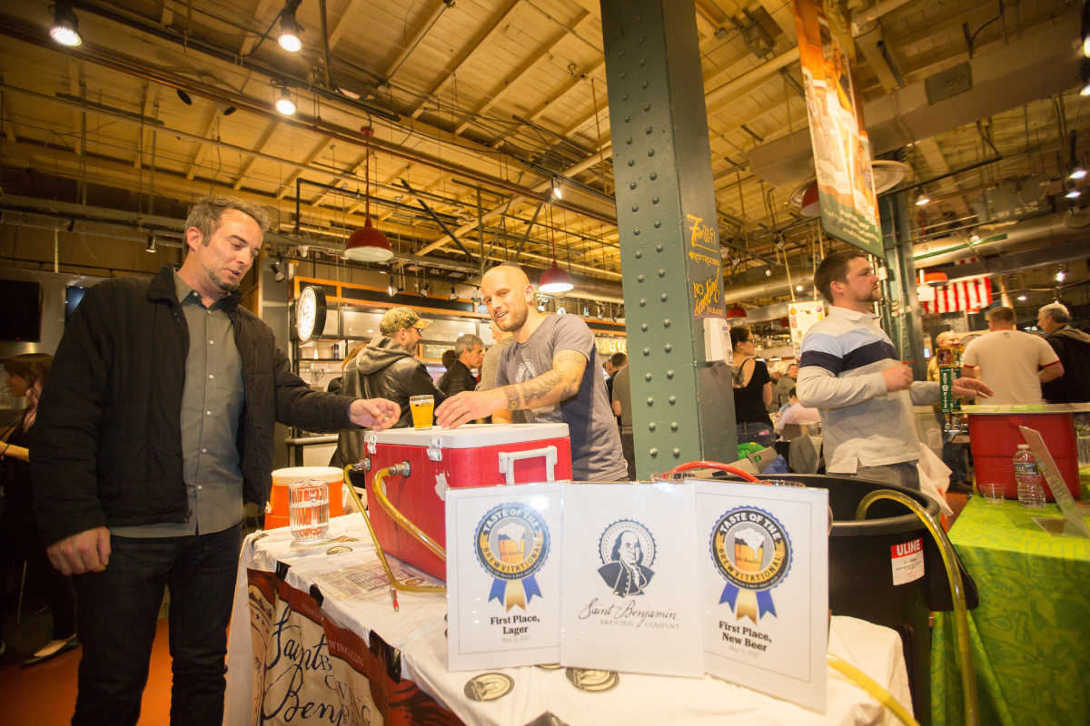 Andrew Foss (center), head brewer at St. Benjamin Brewing Company, pours beer after taking two first-place awards for Best New Beer and Best Lager at the Inquirer's Taste of the Brewvitational at Reading Terminal Market, May 11, 2017.