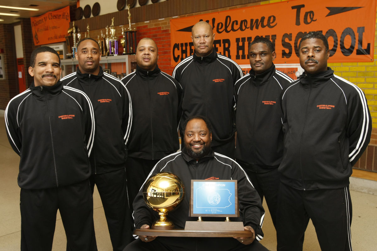 Chester High School basketball coach Fred Pickett Jr. (seated) holds the PIAA  AAAA State Champs 2008 trophy surrounded by assistant coaches from left, Terry Thomas, Keith Taylor, Derick Spence, John Carter, Larry Yarbray, and Kedrick Harris. (Photo from 3/21/08.)