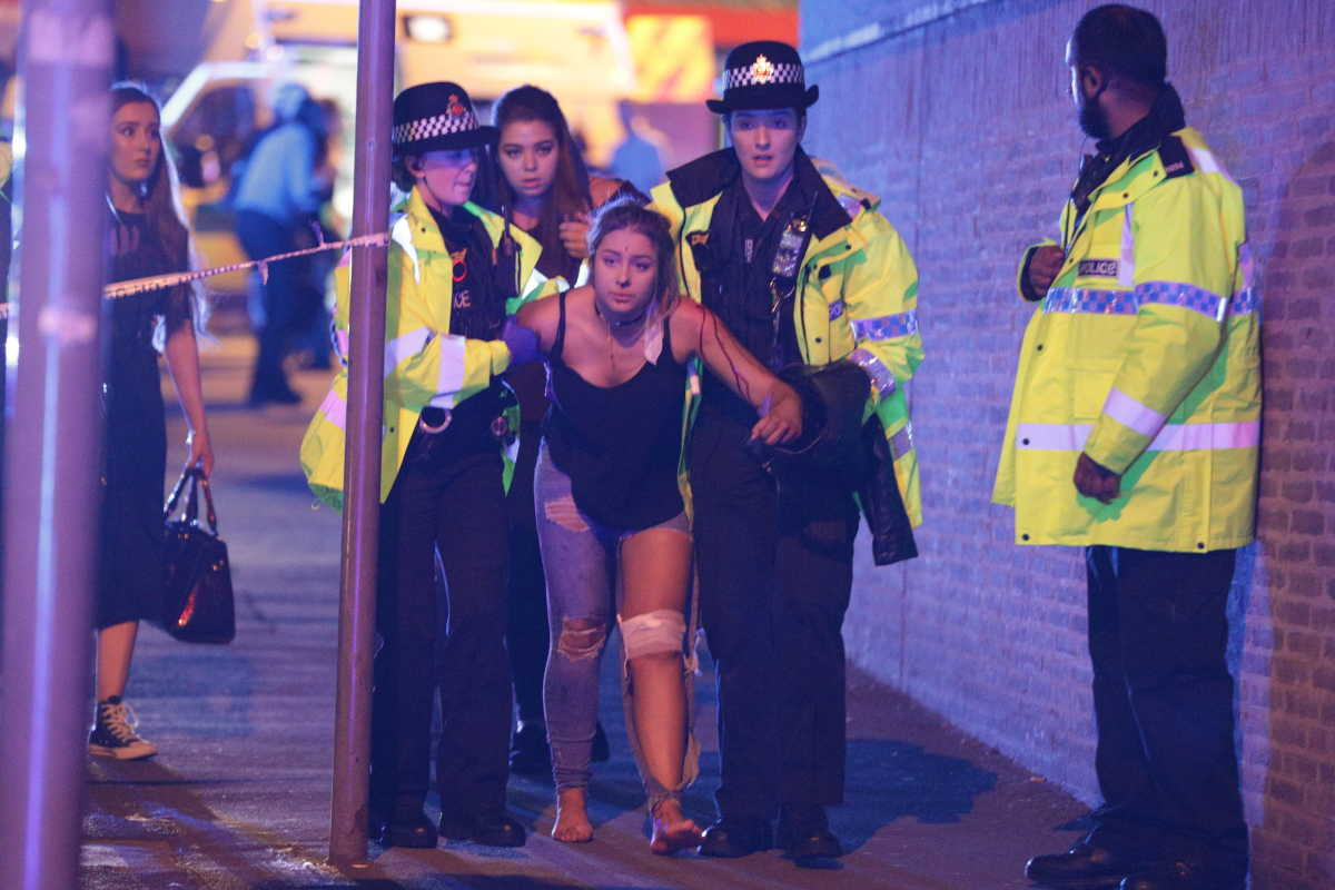 Police and other emergency services help a victim near the Manchester Arena after reports of an explosion at an Ariana Grande concert.